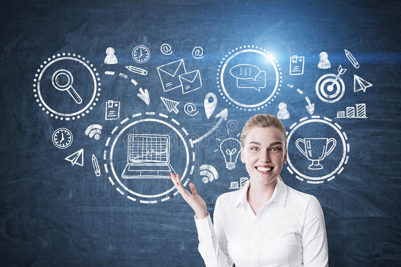 Blond woman showing business trophy. Portrait of a blond businesswoman wearing a white blouse and showing a business trophy sketch drawn on a blue chalkboard royalty free stock photo