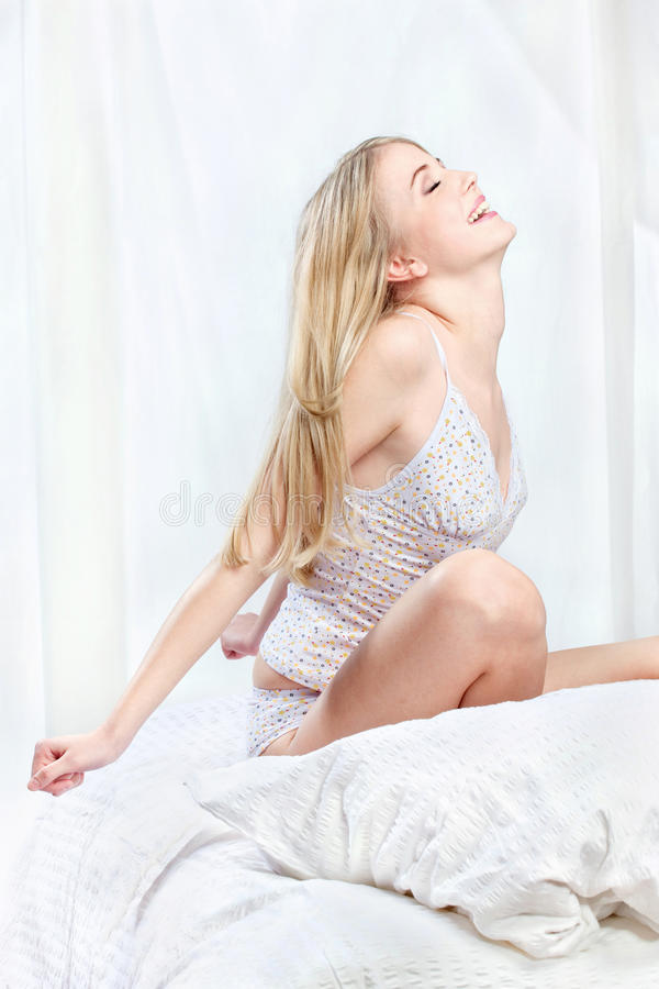Blond Woman Sitting On Bed And Stretching Arms Royalty Free Stock Images