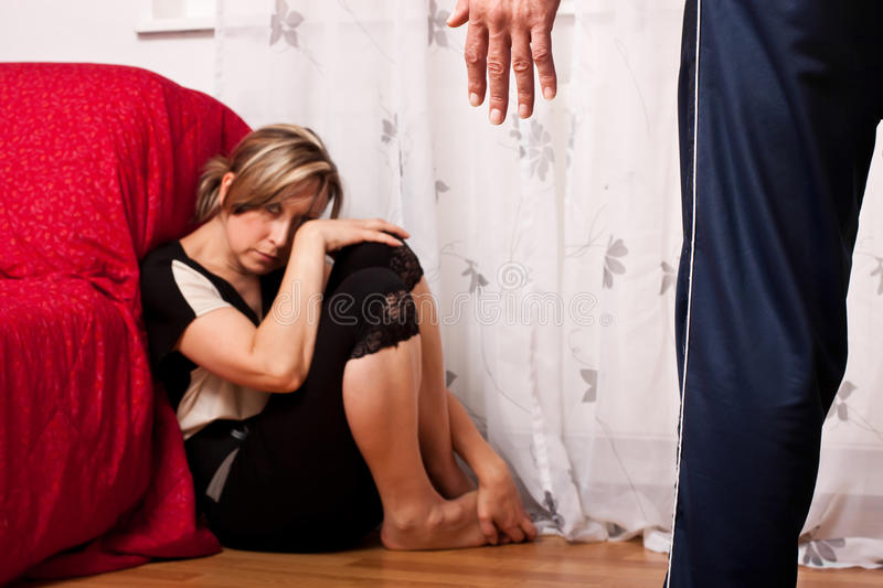 Blond woman sitting in the corner, looking scared. Young woman is a victim of domestic violence stock photos