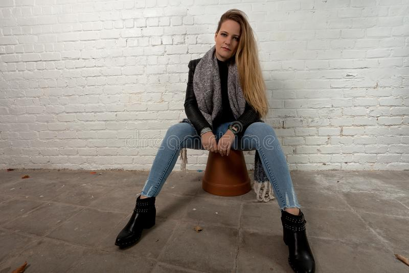 Blond woman sitting green eyes white brick wall. Cool and fashionable woman with long blond hair and green eyes in leather jacket and knitted grey scarf for the stock image
