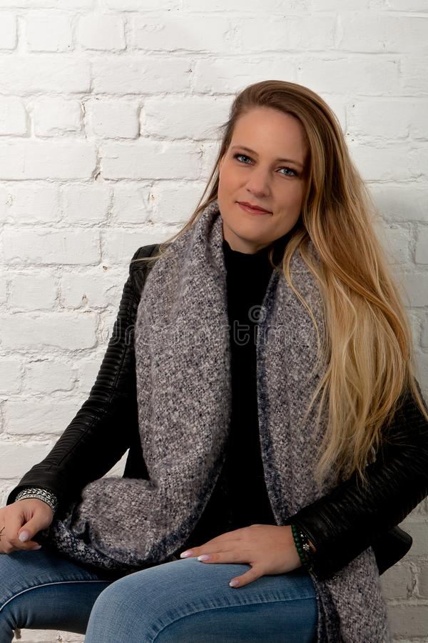 Blond woman sitting green eyes white brick wall. Woman with long blond hair and green eyes in leather jacket and knitted grey scarf for the winter sitting royalty free stock photos