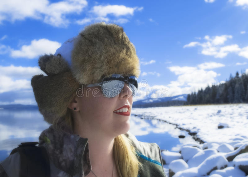 Blond woman by snowy lake in the mountains royalty free stock photo