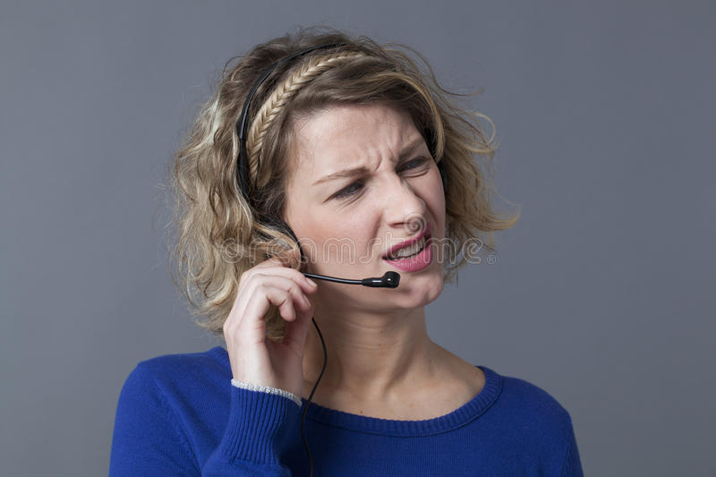 Blond woman squinting while responding to customer. Confusion concept - unhappy young call center assistant frustrated by difficult phone calls on her headset stock photo