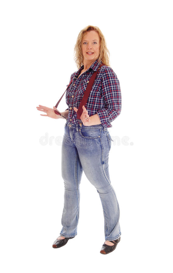 A blond woman standing in jeans and suspender. stock photography