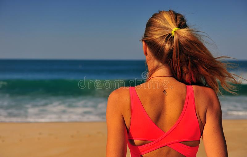 Blond woman standing at sea. On summer stock photography