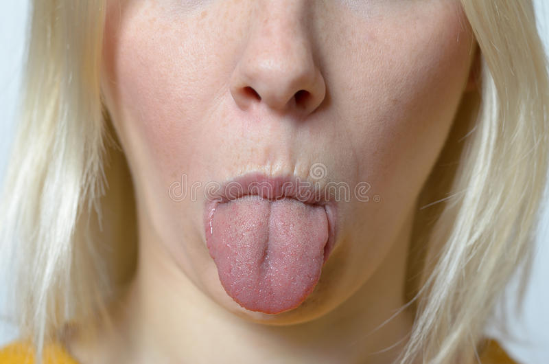 Blond Woman Sticking her Tongue Out. Close Up Blond Young Woman Sticking her Tongue Out at the Camera stock photography