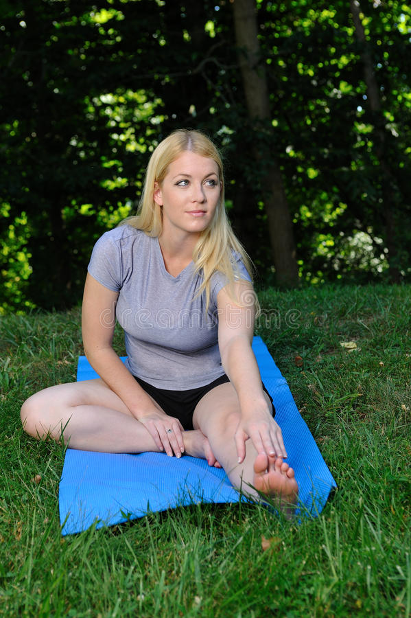 Blond woman stretching - fitness. Beautiful young blond woman stretching her legs (hamstring) in the park before a run stock photography
