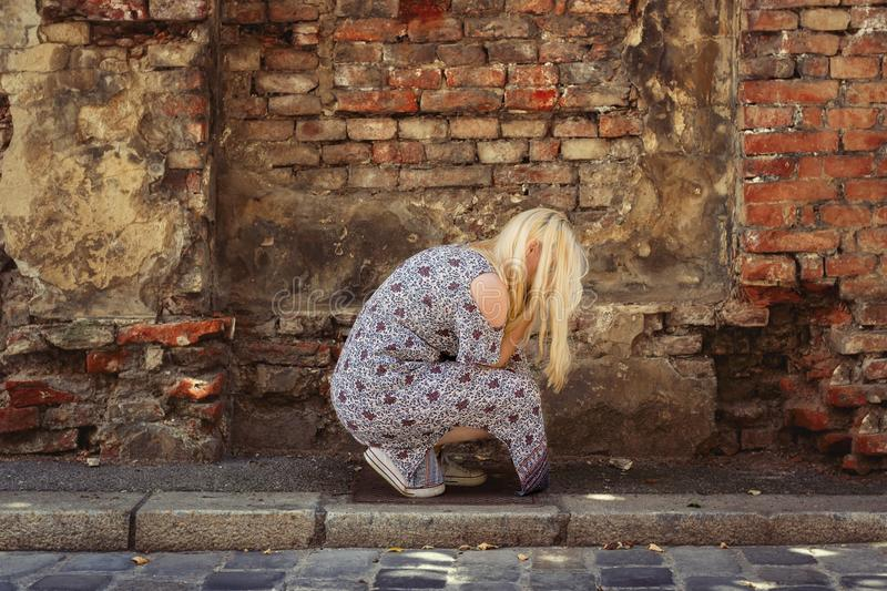 Blond woman in summer dress crouching and crying in front of an old brick wall. Blond woman in summer dress crouching in front of an old brick wall, hiding her stock images