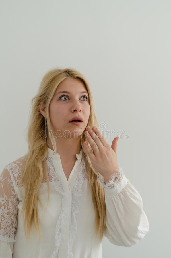 Blond woman with surprised look on her face stock photo