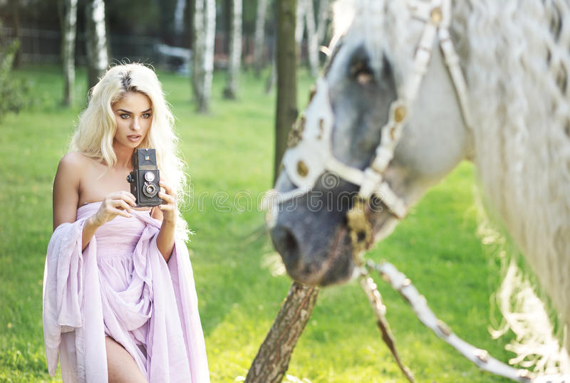 Blond woman taking photos with retro camera royalty free stock photos