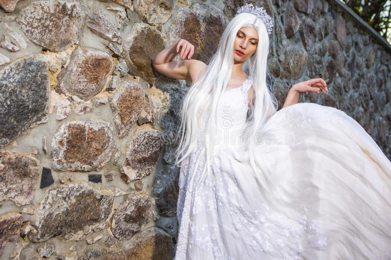 Blond Woman with Tiara and Long White hair Posing in Bridal Flying Dress Against Stone Wall stock photo