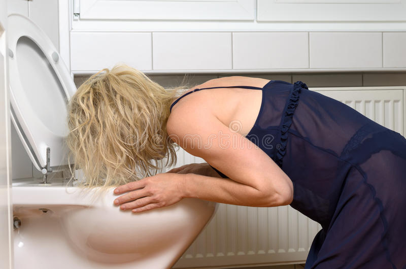 Blond woman vomiting into a toilet. Blond woman in a black dress kneeling down vomiting into a toilet conceptual of an illness or drunkenness after a party stock photos