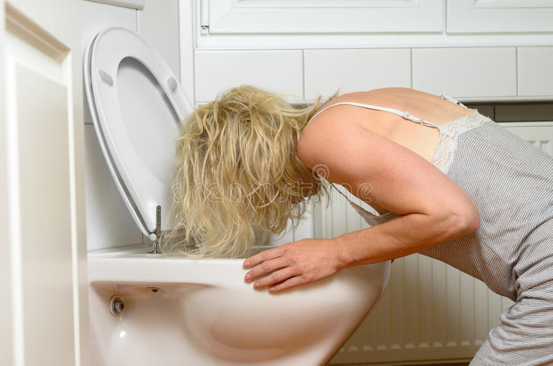 Blond woman vomiting into a toilet. Blond woman in a grey dress kneeling down vomiting into a toilet conceptual of an illness or drunkenness after a party stock photography