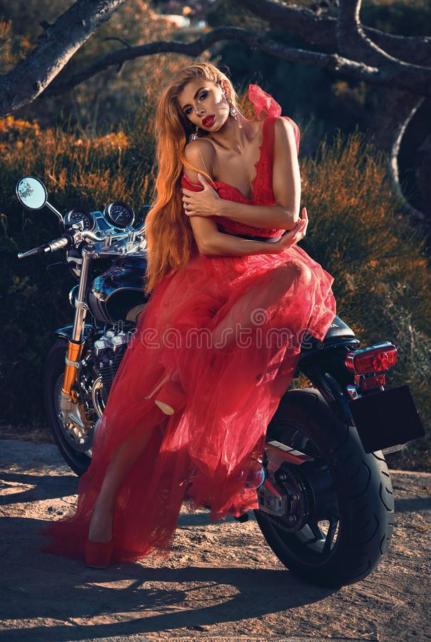 Blond woman wearing red fluffy dress sitting on motorcycle outdoors posing on nature looking at camera royalty free stock photos