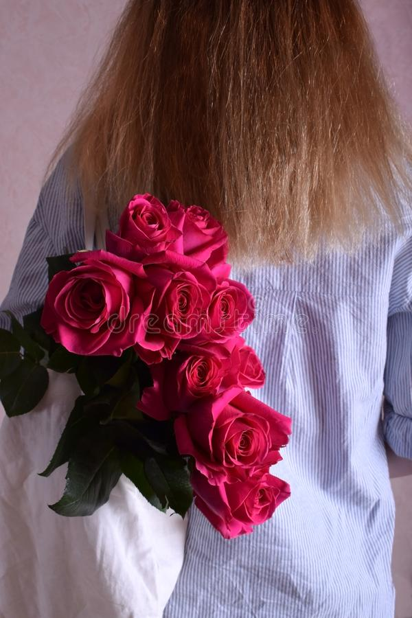 Blond woman wearing a striped shirt is carrying a big bouquet of pink roses in a bag on her shoulder. View from the back stock photo
