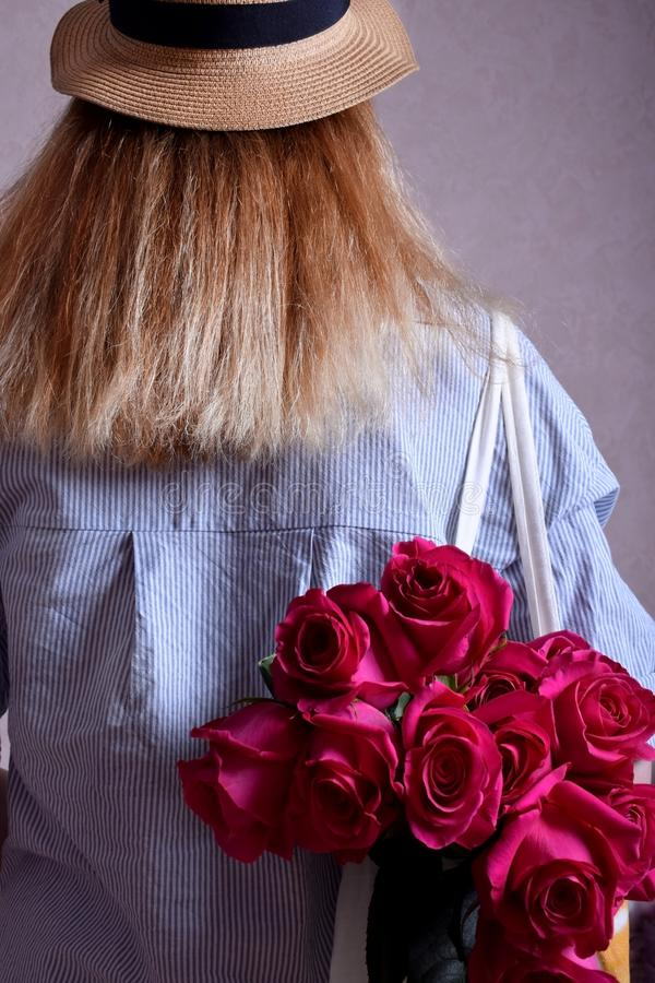 Blond woman wearing a striped shirt is carrying a big bouquet of pink roses in a bag on her shoulder. View from the back royalty free stock photos