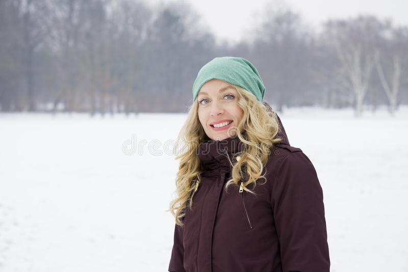 Woman walking on snowy field. Blond woman wearing warm winter fashion walking on snowy field royalty free stock photo