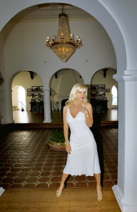 Blond Woman wearing a White Dress. Blond Woman wearin a White Dress in archway royalty free stock photo