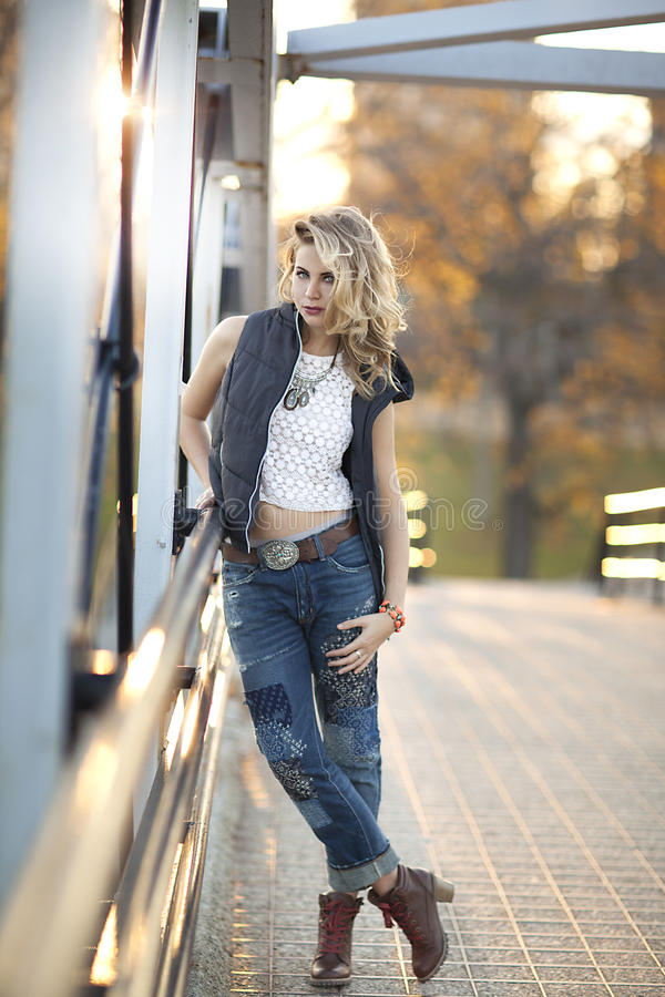 A blond womanl in urban outfit on bridge over Lake Shore Drive. A young blond woman with curly hair and blue eyes wearing a white lace shirt and black vest and stock photography