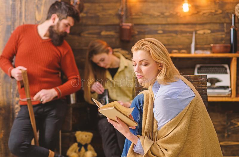 Blond woman concentrated on reading. Female absorbed by fairy tale fantasy, imagination concept. Bearded man whetting. Blond women concentrated on reading stock images
