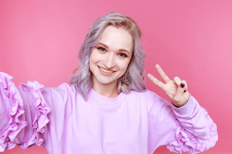 Blond young stylish woman with curly hair showing peace isolated in the studio. stock photos