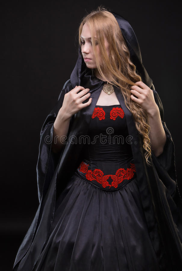 Blond young woman in black cloak. On black background royalty free stock photography