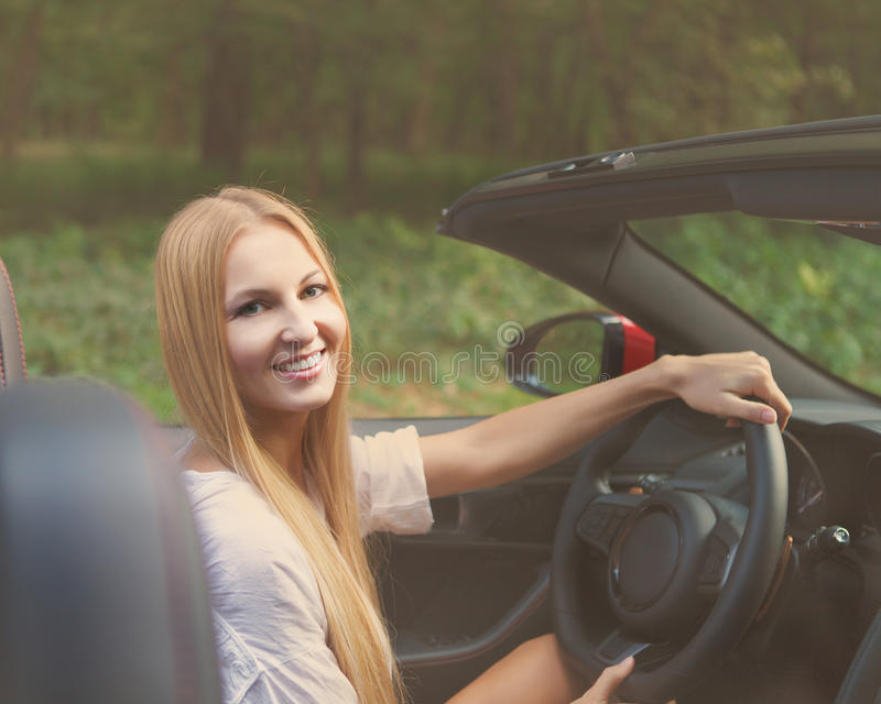 Blond young girl driving a sport car - a Royalty Free