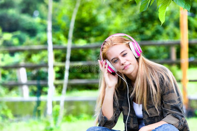 Blond young woman listing to music on headphones. Pretty young blond woman listing to music on headphones, countryside background stock photo