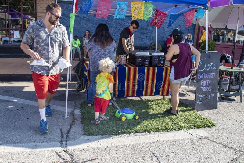 Blond z włosami dziecko kosi łatę sztuczna trawa przed taco stojakiem z zabawkarskim lawnmower podczas gdy dorosli kupują jedzeni obraz stock
