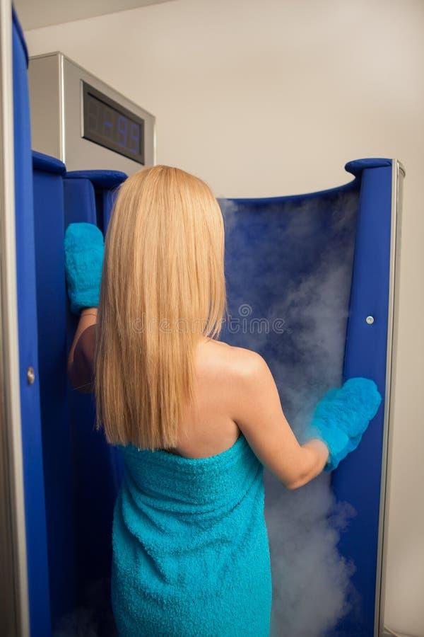 Blond z włosami kobieta wchodzić do cryotherapy sauna budka obraz royalty free