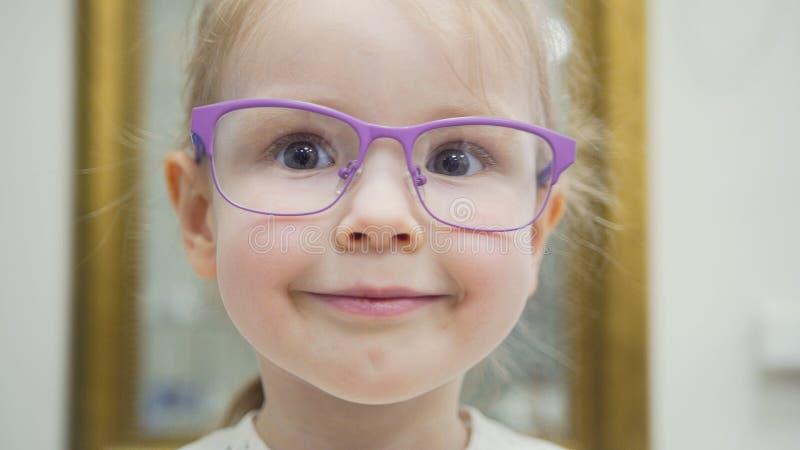 Blonda flickaförsök danar medicinska exponeringsglas som shoppar i oftalmologikliniken - stående royaltyfri fotografi
