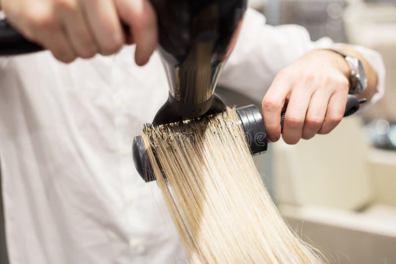 Blonda kvinnas för frisörslaguttorkning hår royaltyfri bild