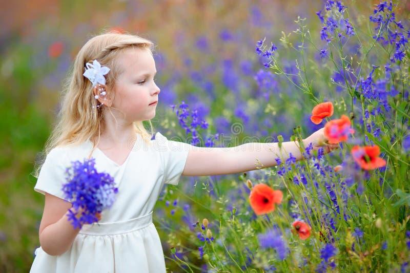 Blonda lösa blommor för en ungeflicka mot efterkrav royaltyfri bild