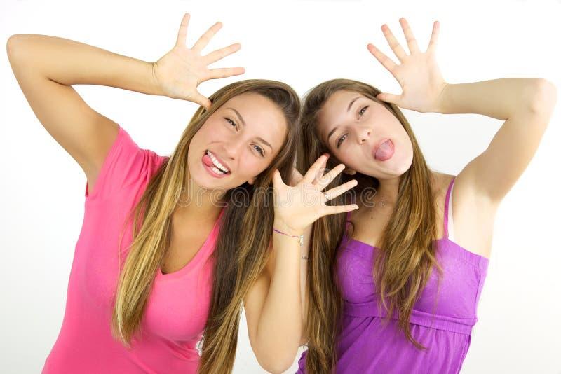 Blonda tonåringar som gör isolerade roliga framsidor arkivfoton