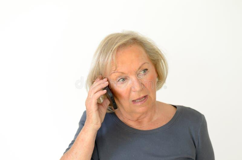 Blonde ältere Frau, die ein Gespräch auf Mobile hat stockfotografie