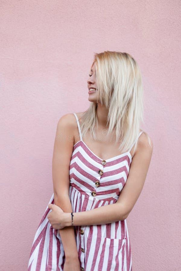 Blonde élégante mignonne de jeune femme dans la robe rayée à la mode posant près d'un mur rose de cru sur la rue dans la ville images stock