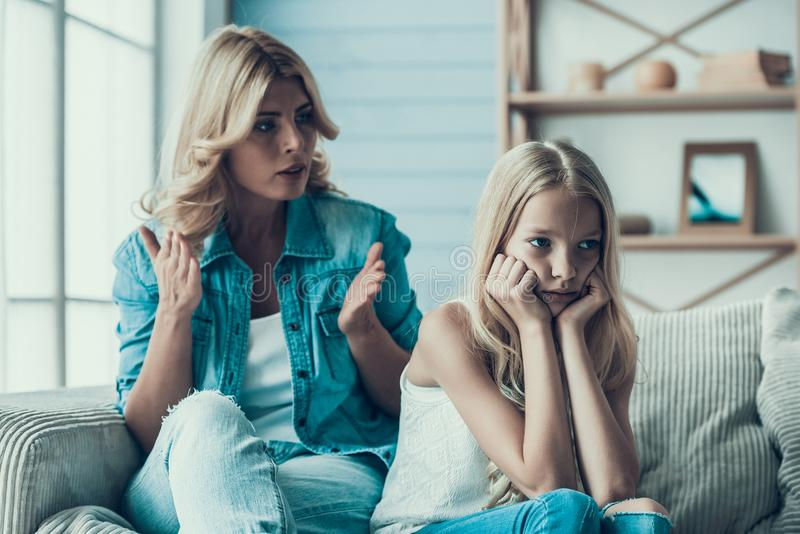 Blonde adult mother brings up naughty girl teenager. Concept of correct parenting royalty free stock photo