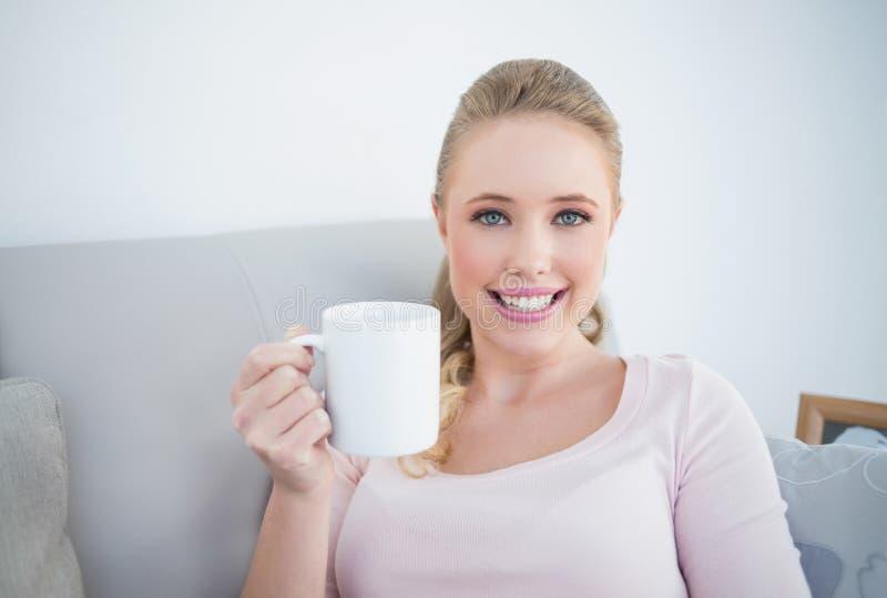 Blonde allègre occasionnelle tenant une tasse photo libre de droits