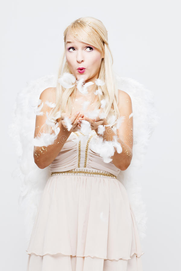 Blonde Angel blowing feathers royalty free stock photo
