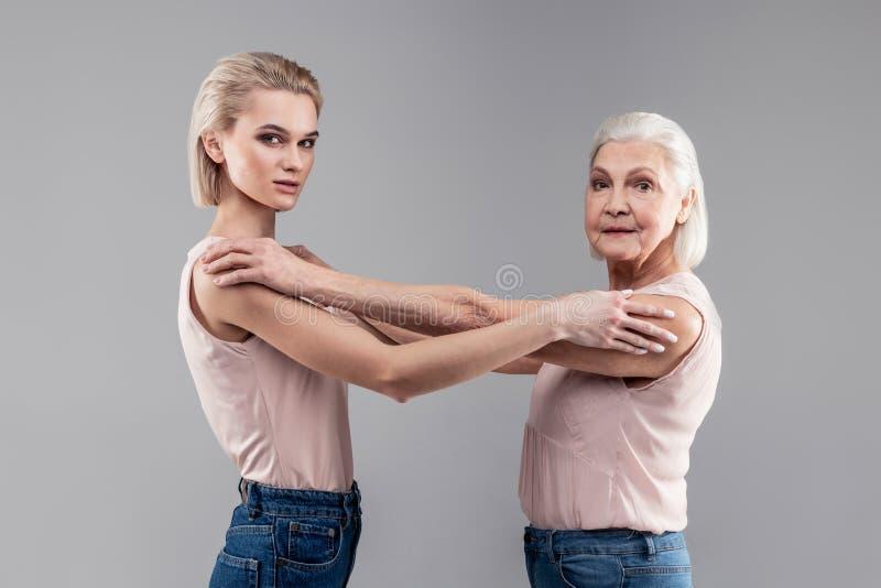 Blonde anziehende Frau und grau-haarige ältere Dame, die Schultern sich berührt stockbild