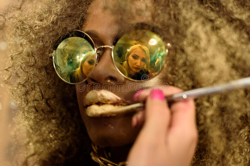 Blonde artist painting gold lips with tassel reflected in the sunglasses of fashion African or Black American model wearing bright stock photo