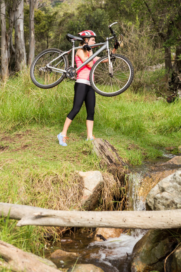 Blonde athlete carrying her mountain bike royalty free stock photography