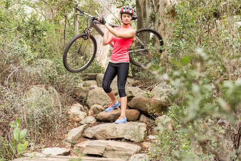 Blonde athlete carrying her mountain bike over rocks stock images