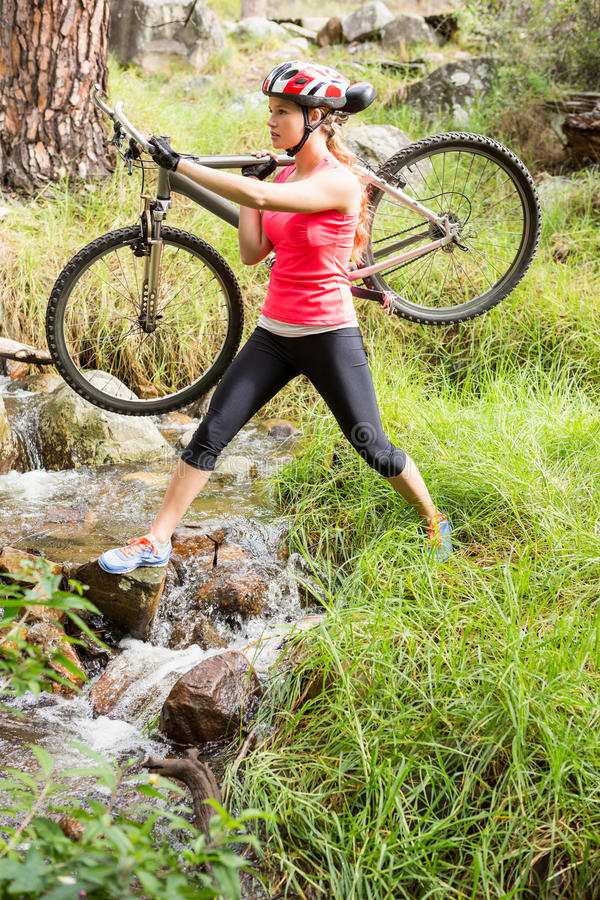 Blonde athlete carrying her mountain bike over stream stock photo