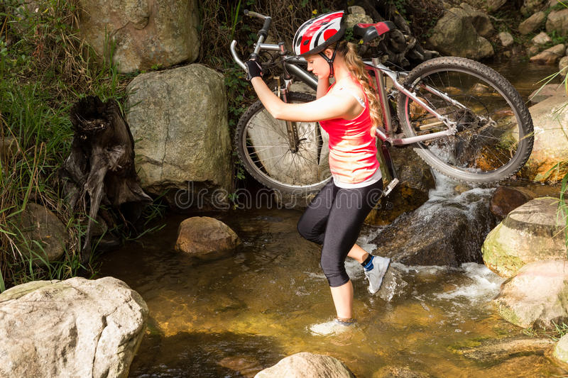 Blonde athlete carrying her mountain bike over stream royalty free stock images