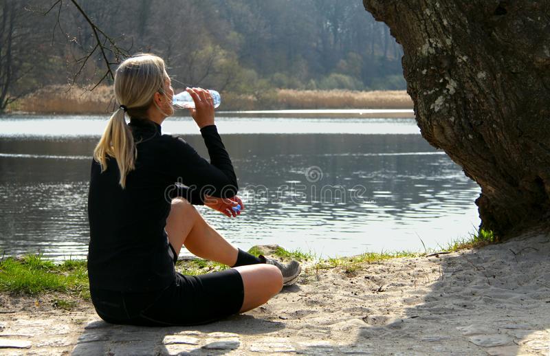 Blonde athlete girl sitting on ground to relax after jogging drinking water under a tree on a lake shore. Blonde athlete woman sitting on ground drinking water stock photo