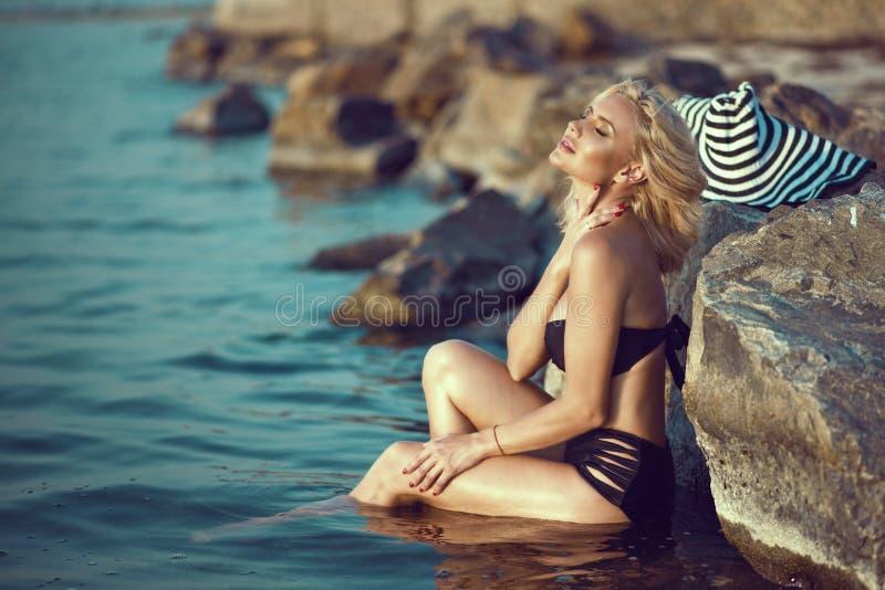 Blonde atractivo bronceado magnífico en el traje de baño negro que se sienta en el agua en las piedras grandes que acaricia su cu imagen de archivo libre de regalías