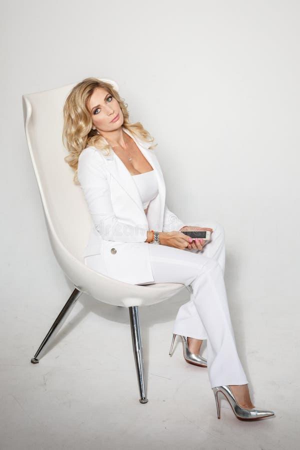 Blonde atractivo hermoso en un traje blanco que presenta en el fondo blanco fotos de archivo libres de regalías