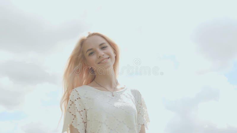 Blonde Aufstellung des jungen russischen Mädchens gegen einen weißen Himmel an einem Sommertag lizenzfreies stockbild