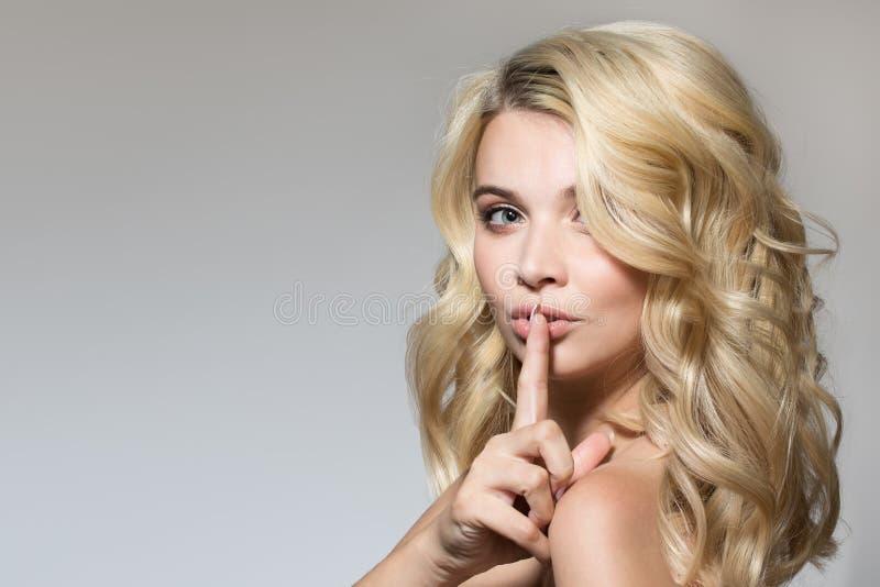 Blonde avec des boucles sur un fond gris images stock